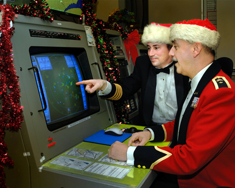 Two members of Canadian Forces check the radar screen in preparation for tracking Santa Claus.