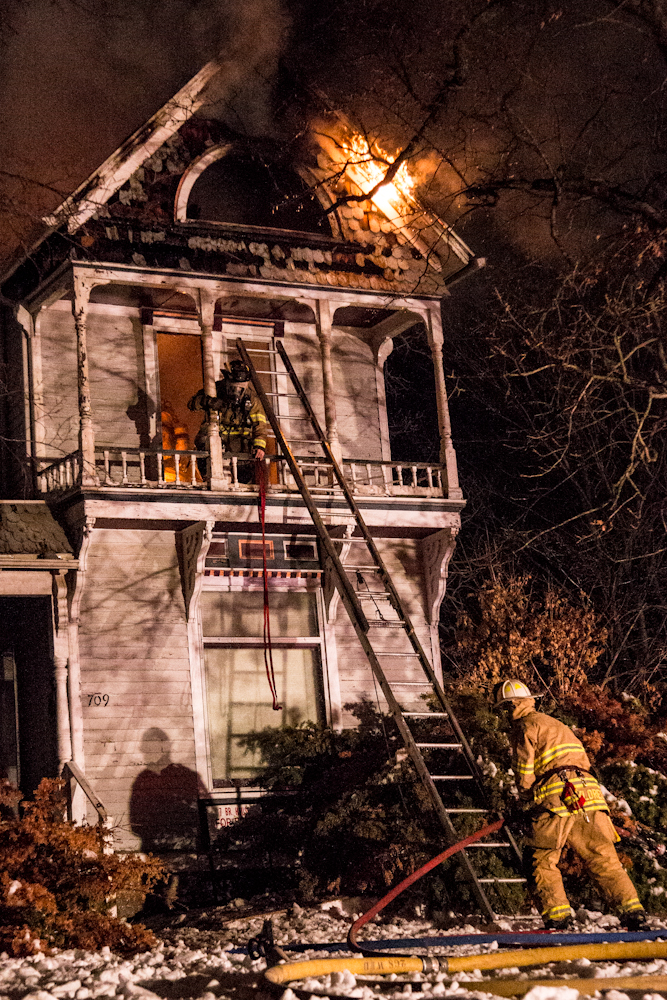 Fire breaks out in the attic. The firefighter on the upper level drops down some rope to the firefighter below. (Photo by ANDREW MATHER, Muleskinner Photo Editor)