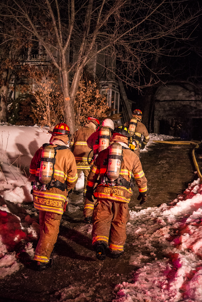 A team of firefighters heads toward the house.