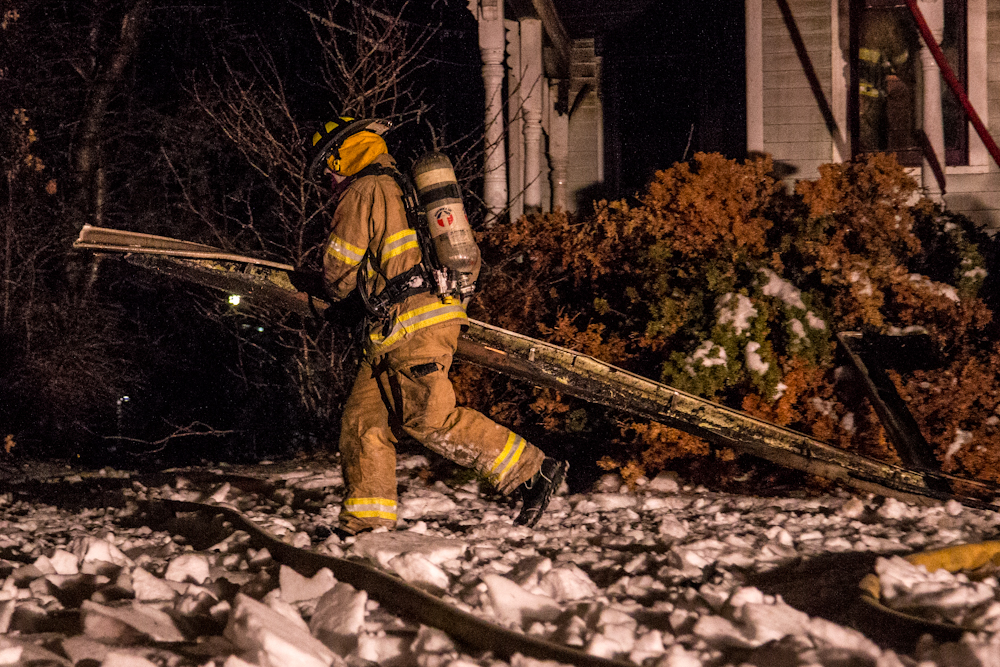 A firefighter removes a piece of debris from the house.