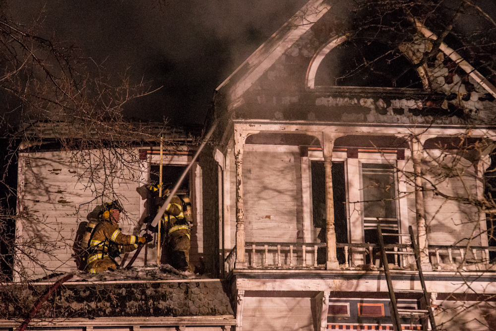 Firefighters use the hose to get the fire near the roof under control Sunday morning at 709 S. Holden St.