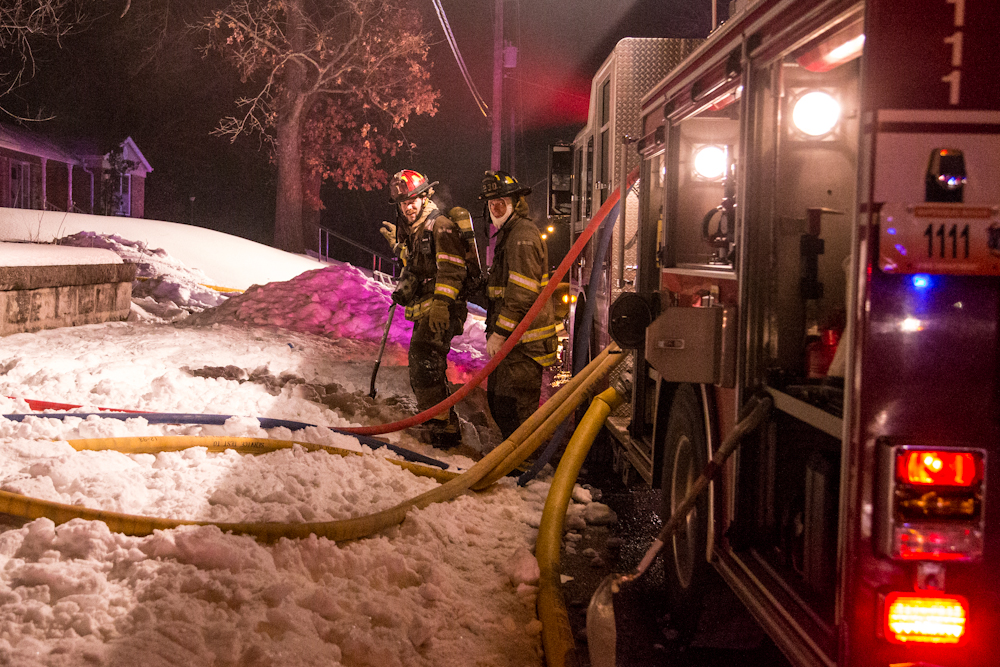 Firefighters watch out for their fellow crew members as they enter the house.