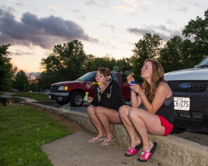 (Photo by Andrew Mather, digitalBURG) UCM seniors and roommates Liana Sharp (left), a commercial photography major, and Carrie Hall, a psychology major, take a break from their daily responsibilities to enjoy the beautiful weather at Lions Lake on Thursday evening. Liana and Carrie embrace their inner child as they blow bubbles while watching the sunset over the lake.