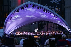 "The Kansas City Symphony, led by conductor Michael Stern (center stage) performs Tchaikovsky's ""1812, Overture solennelle"" on stage underneath a star-spangled canopy in front Union Station."
