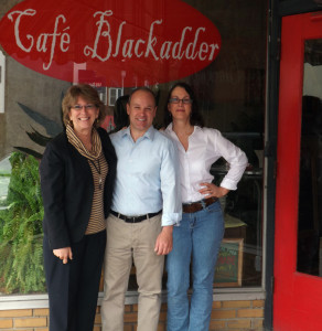 (Courtesy photo) From left, City Manager Paula Hertwig Hopkins, Main Street President Jason Elkins, and Café Blackadder owner Sandy Irle pose in front of the café after the announcement about the business being awarded the first downtown façade grant.