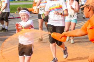 A young girl closes her eyes as she runs through a burst of orange color.