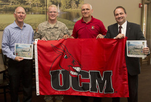 University of Central Missouri alumnus Patrick Stueve, second from left, presents one of two UCM flags with the Mule head logo to President Charles Ambrose, left. Ambrose had the flags sent to Stueve in Afghanistan.  Joining Stueve and Ambrose for the presentation were Jeff Huffman, third from left, director of Military and Veteran Services, and Tony Monetti, assistant dean of aviation and executive director of the Max B. Swisher Skyhaven Airport.