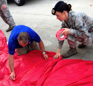 Senior Airman Jessica Lindblom assists a member of the Kansas City Royals events team in taping a tear in the 300-foot American flag moments before the 120-member group of military personnel from Whiteman Air Force Base presented the flag prior to the start of the game.