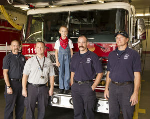 From Left: Captain Terry Hill, Fire and Emergency Prevention Officer Jeremy VanWey, Karsten Eckhoff, 6, and Firefighter Specialist JD Gudde, and Firefighter Specialist Doug Brookshier tour the firestation celebrating Eckhoff's