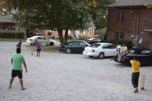 PHOTO BY TYRAN BROOKS FOR THE MULESKINNER Srni Srinivas (right) prepares to bowl in a backyard cricket match with his roommates in his apartment complex's gravel driveway.
