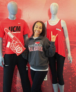 PHOTO BY BETHANY SHERROW / ASSISTANT NEWS EDITOR Sierra Seals works at the new University Store. She stands next to some mannequins and wears a Mules and Jennies foam finger to show her UCM pride.