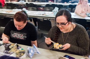 PHOTO BY MARIE NABORS / PHOTOGRAPHER Katie Oparnico (left), a senior ceramic studio art major, and Shannon Commerford, a freshman art education major, create a couple of colorful fish and enjoy some sushi.
